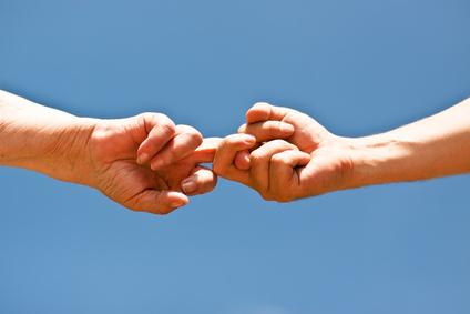Zwei Finger ziehen vor blauem Himmel aneinander