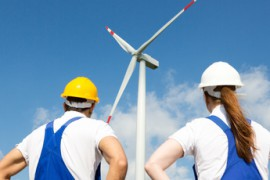 Engineers or installers posing in front of wind energy turbine